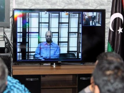 Saif Gaddafi appears via video link in a Libyan courtroom. © EPA