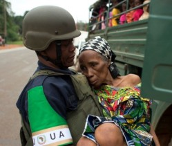 An African Union peacekeeper assists a woman impacted by the conflict in the Central African Republic. © AP/Rebecca Blackwell