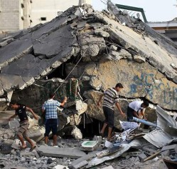 Men inspect the rubble of a destroyed building in Gaza in summer 2014. © Getty