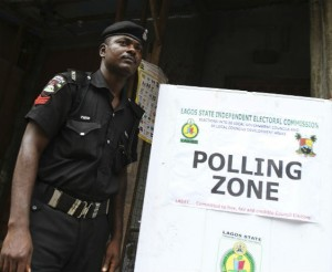A police officer stands watch over a polling place in Nigeria. © Akintunde Akinleye/Reuters