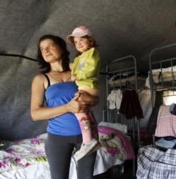 A woman holds her daughter in a Ukrainian refugee camp. © Reuters/Eduard Korniyenko
