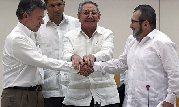 Cuban President Raúl Castro, centre, holds the hands of Colombian President Juan Manuel Santos, left, and top leader of the Revolutionary Armed Forces of Colombia (Farc) Rodrigo Londono 'Timochenko' Echeverri (right) during a press conference announcing the reaching of an agreement © Alejandro Ernesto/EPA