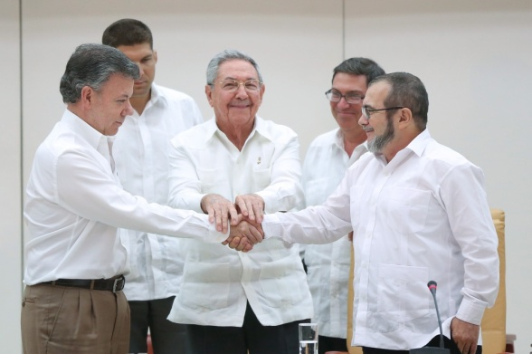 Cuba's President Raul Castro (C) stands as Colombia's President Juan Manuel Santos (L) and FARC rebel leader Rodrigo Londono, better known by the nom de guerre Timochenko, shake hands in Havana