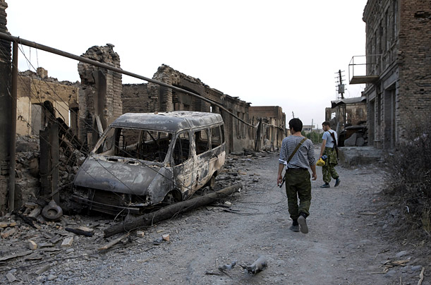 Ossetian volunteers pass a burned out van on a street in Tskhinvali.TIME