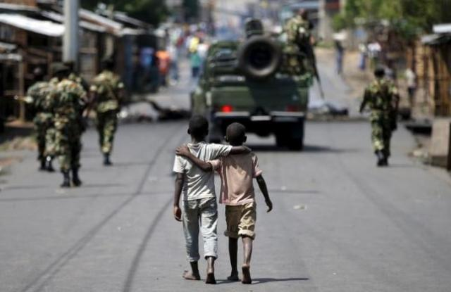 Boys walk behind patrolling soldiers in Bujumbura
