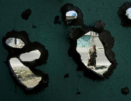 AP_An Ossetian woman, seen through a bullet hole in the gates of a house, walks in Tskhinvali, capital of Georgian breakaway region of South Ossetia.