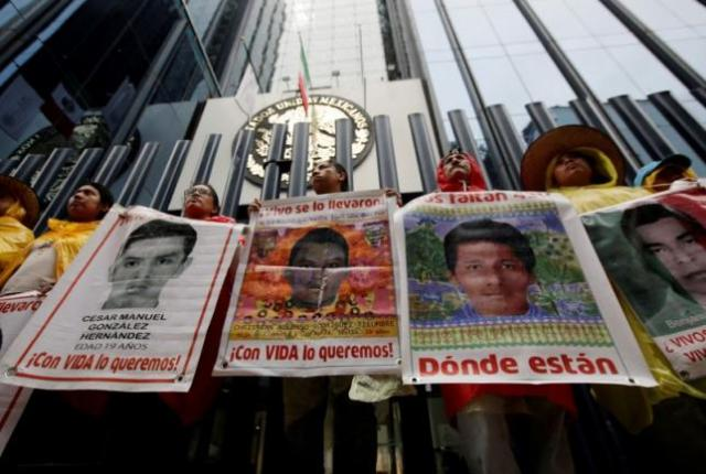 Relatives hold posters with images of some of the missing students of Ayotzinapa College Raul Isidro Burgos as they protest in Mexico City
